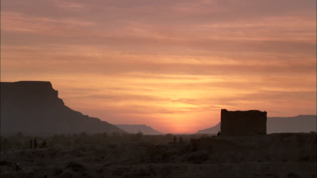 A rocky desert hill and a stone tower stand silhouetted against a glowing orange sky in Shibam Yemen.
