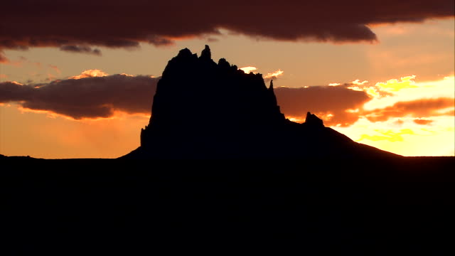 vídeos de stock e filmes b-roll de ws rocky desert landscape terrain in silhouette hills mountain peak clouds w/ orange tint in blue sky bright sunlight on horizon - cultura navajo