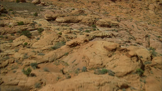 AERIAL Rocky desert terrain, and a valley with a river meandering through