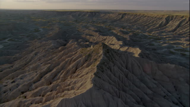 rocky, eroded mountains fill a wide canyon in badlands national park. available in hd. - badlands national park video stock e b–roll