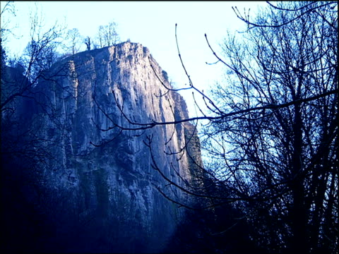 rocky face of matlock tor behind bare branches derbyshire - felswand stock-videos und b-roll-filmmaterial