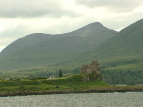 vidéos et rushes de rocky green coastline, woodline, hills, scottish castle on coast, tranquil, picture postcard - mull