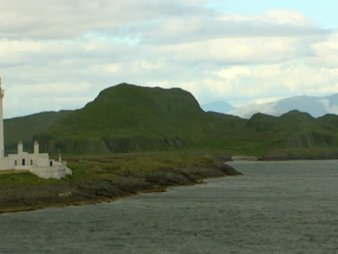 vidéos et rushes de rocky green landscape, passing lighthouse, dull, calm sea, tranquil, natural, relaxing - mull