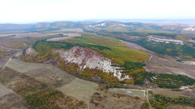 aerial: rocky hills with colorful trees and bushes in autumn - deciduous stock videos & royalty-free footage