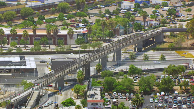 WS AERIAL POV Rocky hilltop revealing pedestrian bridge over roadway at international border crossing between Tijuana Mexico and San Diego / San Diego, California, United States