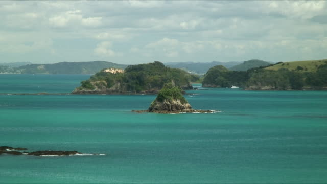 ms ws ha zo rocky island in turquoise sea surrounded by lush coast, bay of islands, new zealand - bay of islands new zealand stock videos & royalty-free footage