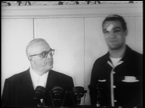 vidéos et rushes de rocky marciano in bandages standing next to man at press conference / after walcott fight - 1952