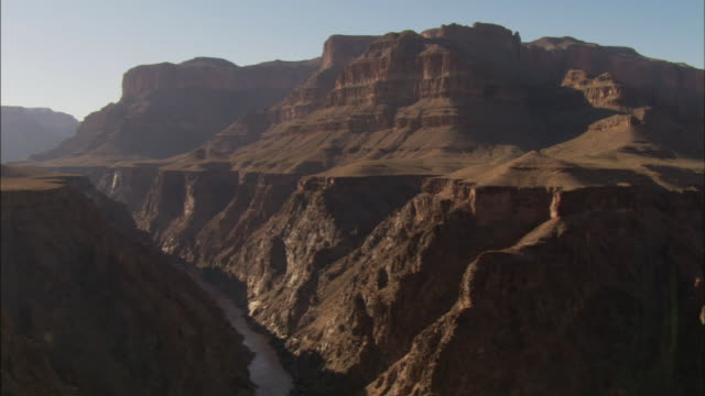 rocky mesas overlook steep canyon walls along the colorado river. - グランドキャニオン点の映像素材/bロール