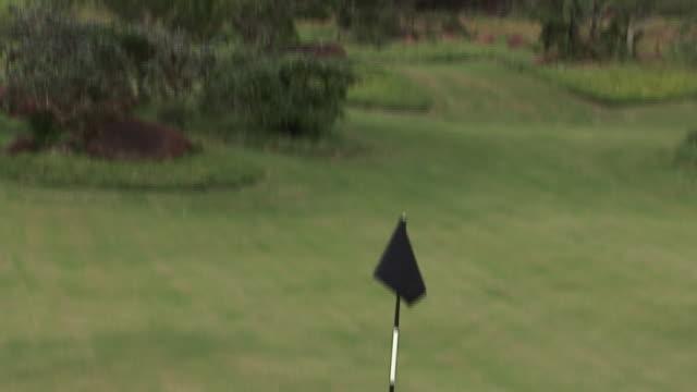 a rocky mountain overlooks a golf course. available in hd. - bandierina da golf video stock e b–roll