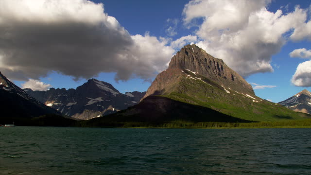 A rocky mountain towers behind Swiftcurrent Lake in Glacier National Park.