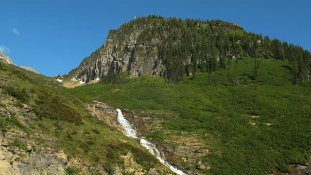 a rocky mountain towers over a waterfall in glacier national park. - glacier nationalpark stock-videos und b-roll-filmmaterial