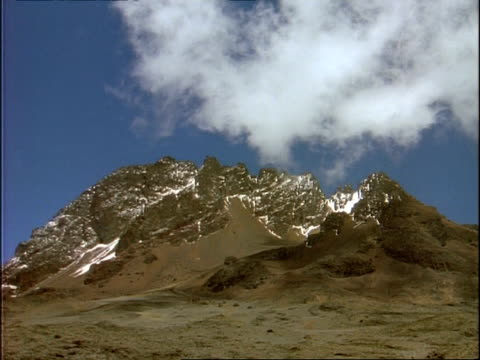 WA Rocky mountain with small amount of snow, against blue sky, wispy clouds, Ethiopia, Africa
