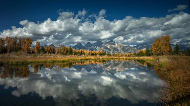 rocky mountains reflected in lake, grand teton national park, wyoming - montagne rocciose video stock e b–roll