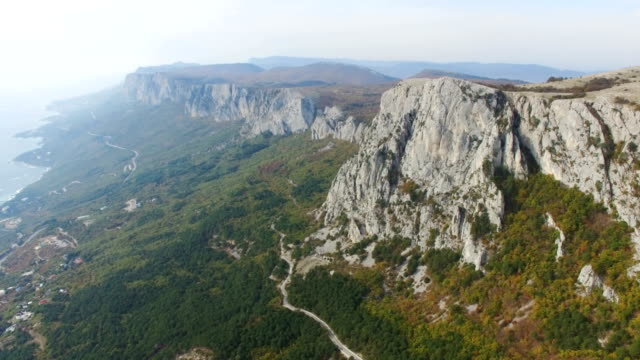 AERIAL: Rocky mountains with green forests and blue sea below
