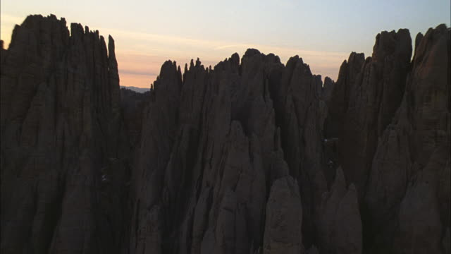aerial rocky outcroppings and crags in mountain foothills as the sun sets / south dakota, united states - south dakota stock videos and b-roll footage
