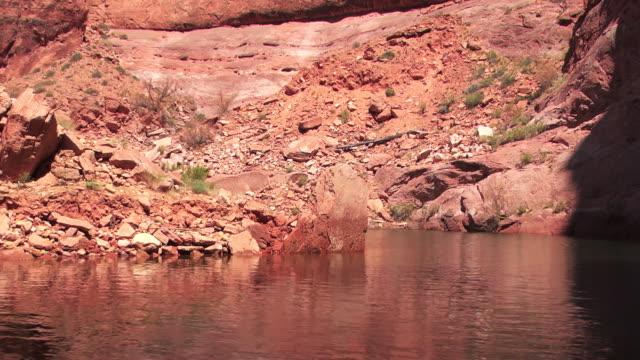 vidéos et rushes de rocky riverbanks dotted with desert vegetation cast reflections on the surface of a river. - grès