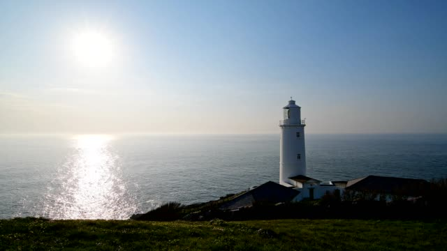 rocky shore with trevose head lighthouse with sun, trevose head lighthouse, padstow, cornwall, england, united kingdom, europe - cornwall england stock videos & royalty-free footage