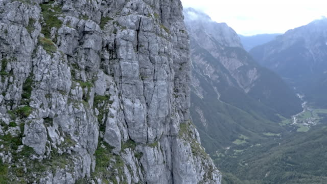 aerial rocky side of a high range mountain - rock face stock videos and b-roll footage