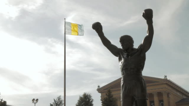 LA Rocky statue, Philadelphia flag flying on flagpole, and Philadelphia Museum of Art facade / Philadelphia, Pennsylvania, United States