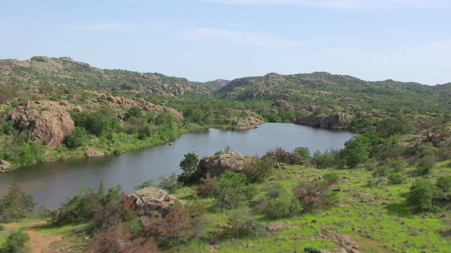 ws aerial rocky terrain and water in wichita mountains / oklahoma, united states - wichita stock-videos und b-roll-filmmaterial