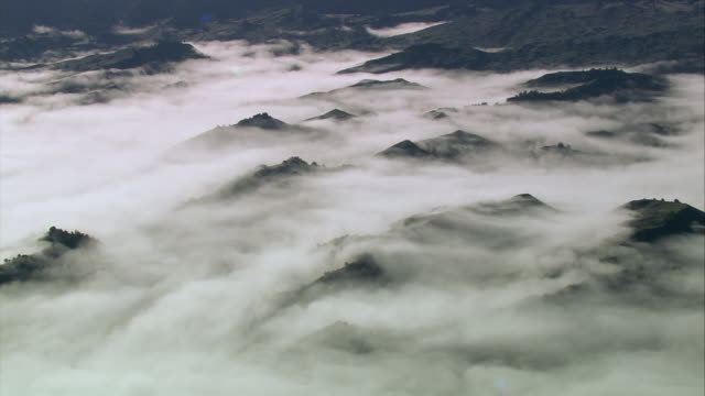 aerial rocky tips of mountains showing above a blanket of clouds / manawatu-wanganui, new zealand - tongariro national park stock videos & royalty-free footage
