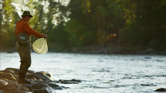 stockvideo's en b-roll-footage met rod and reel fisherman casting in river usa - hengel uitwerpen