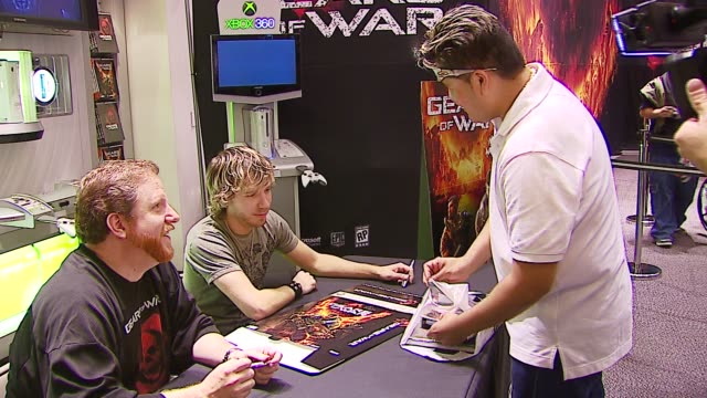 rod fergusson and cliff bleszinski signing autographs at the xbox 360 gears of war retail launch at in los angeles, california. - ギアーズオブウォー点の映像素材/bロール