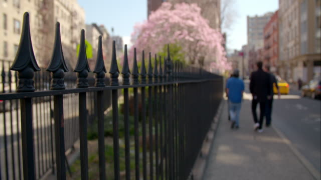 A rod iron fence surrounds a small park in spring in Greenwich Village on 7th Avenue in Manhattan.