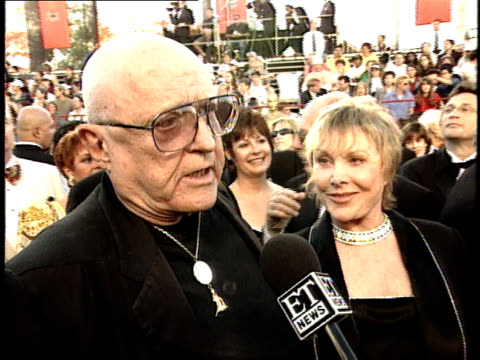 Rod Steiger talks to a reporter on the red carpet at the 70th Annual Academy Awards