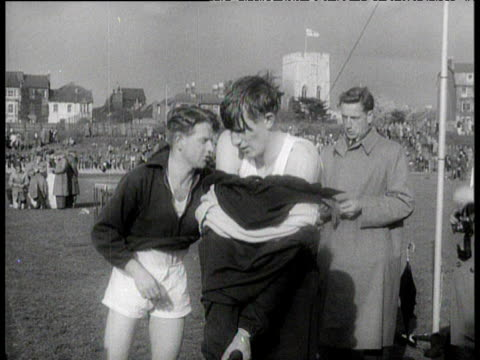 vídeos de stock e filmes b-roll de roger bannister and chris chataway remove tracksuits pre men's mile, iffley road, oxford; 6 may 1954 - fato de treino