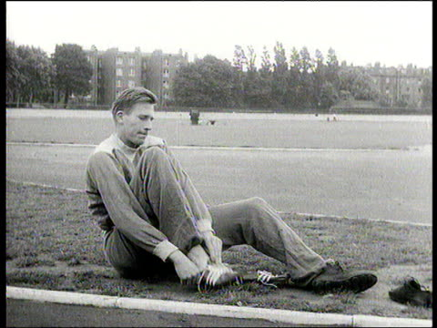 roger bannister wearing tracksuit putting on shoes as he sits by side of running track england 1954 - bannister stock videos & royalty-free footage