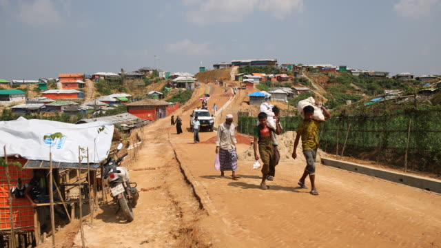 kutupalong ukhiya near cox´s bazar bangladesh october 16 2018 rohingya are carrying goods through the camp huts canbe seen as well in the refugee... - rohingya kultur stock-videos und b-roll-filmmaterial