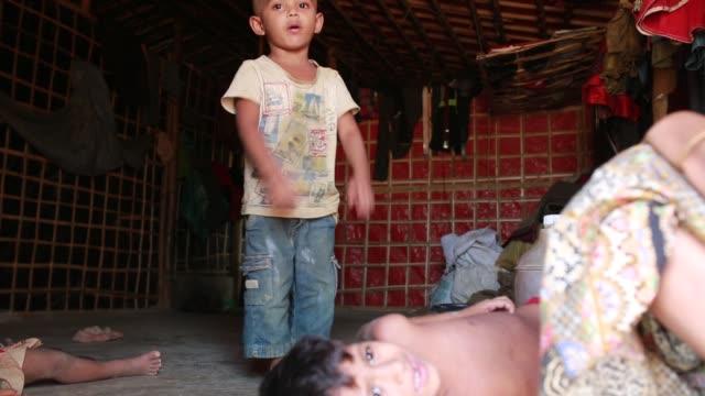 vídeos y material grabado en eventos de stock de cox's bazar bangladesh may 04 a rohingya child fled from ongoing military operations in myanmar's rakhine state preparing his class lesson inside his... - un día en la vida