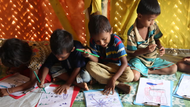rohingya children are drawing pictures in a project for education, financed by ngos. refugee camp of the rohingyas near cox's bazar in bangladesh in... - bamboo plant stock-videos und b-roll-filmmaterial