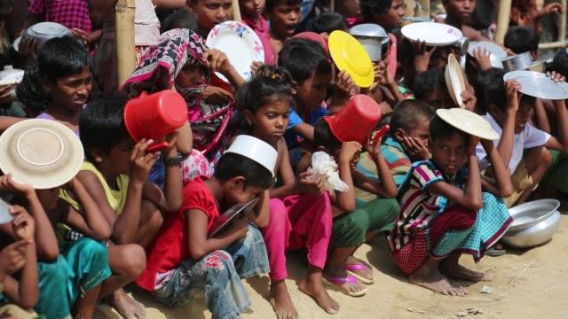 rohingya children wait for food aid near the palongngkhali makeshift camp in teknaff, bangladesh on october 06, 2017. bangladesh said it would be one... - 移民点の映像素材/bロール