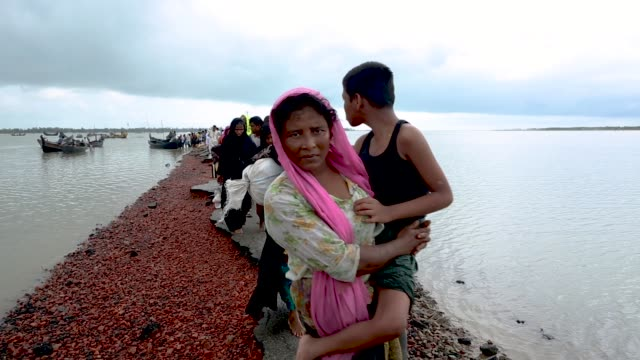 rohingya muslim refugees walk along the remains of a road after arriving on a boat from myanmar on september 08 2017 in whaikhyang bangladesh... - rohingya kultur stock-videos und b-roll-filmmaterial