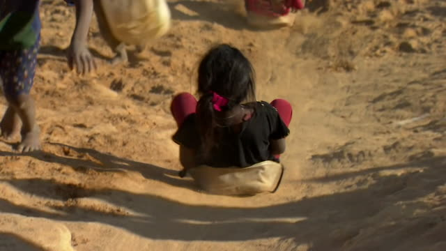 Rohingya refugee children sliding down a hill on a refugee camp in Bangladesh