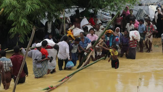 rohingya refugees balance on bamboo as they try to cross a stream the monsoon rains create challenges for the displaced rohingya people in kutupalong... - emigration and immigration stock videos & royalty-free footage