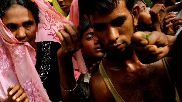 rohingya refugees wait for sacks of rice to be distributed on september 10, 2017 in whaikhyang, bangladesh. recent reports have suggested that around... - 移民点の映像素材/bロール