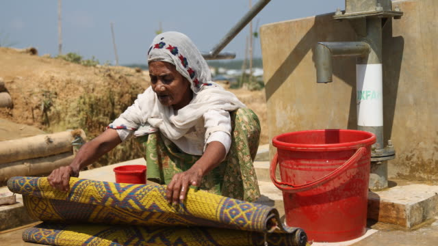 rohingya woman in a hijab cleans a carpet at a fountain in the refugee camp of the rohingya people near cox's bazar in bangladesh in camp 4 in... - united nations stock videos & royalty-free footage