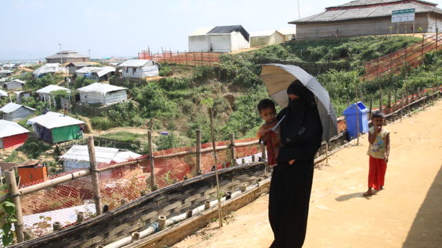 kutupalong ukhiya near cox´s bazar bangladesh october 16 2018 a rohingya woman wearing a black niqab holding her baby in her right hand an umbrella... - cox basar stock-videos und b-roll-filmmaterial