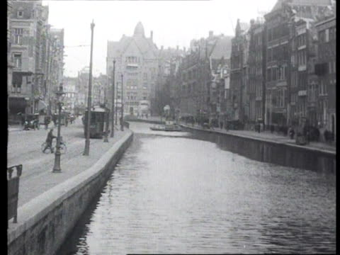 rokin in direction of dam with tram along water pedestrians walking across lange brug / amsterdam noordholland netherlands - 1923 stock videos & royalty-free footage