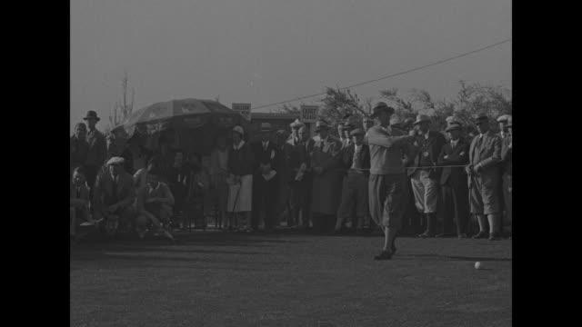 rokuzo asami tees off at the los angeles open / high angle of macdonald smith as he drives ball / vs gallery walks course, moving to 18th green /... - pgaイベント点の映像素材/bロール