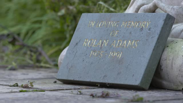 interview with rolan's parents on eve of 30th anniversary; england: ext statue and memorial plaque 'in loving memory of rolan adams'. memorial plaque... - crime and murder stock-videos und b-roll-filmmaterial
