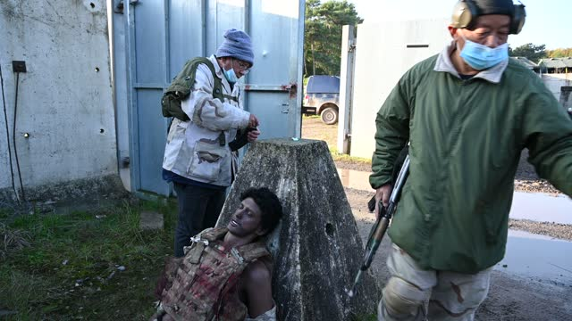 """vídeos de stock, filmes e b-roll de role-play actors load blank rounds before taking part in a scenario, or """"serial"""", at a replica village during a mission rehearsal exercise ahead of... - ilhas do oceano atlântico"""