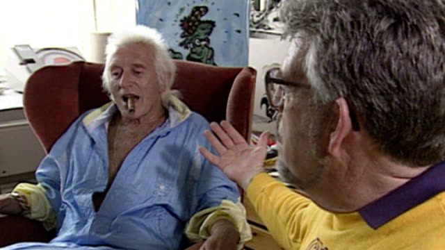 rolf harris victim speaks of her ordeal 1992 location unknown int 'itv news' logo jimmy savile appearing on tv show with rolf harris and rolf joking... - ジミー サヴィル点の映像素材/bロール