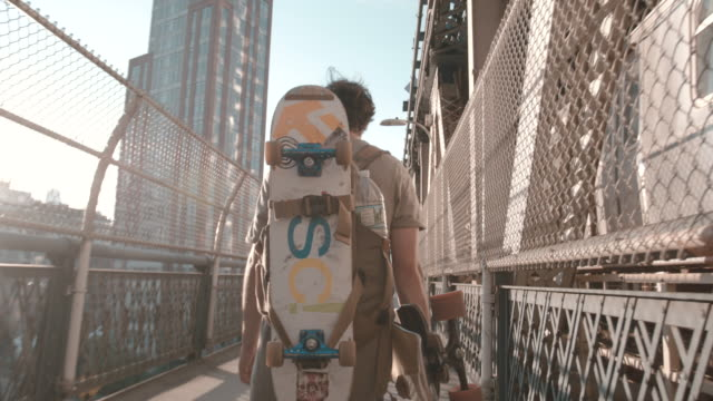 B Roll of a young, caucasian skateboarder walking over NYC's Manhattan Bridge - 4k