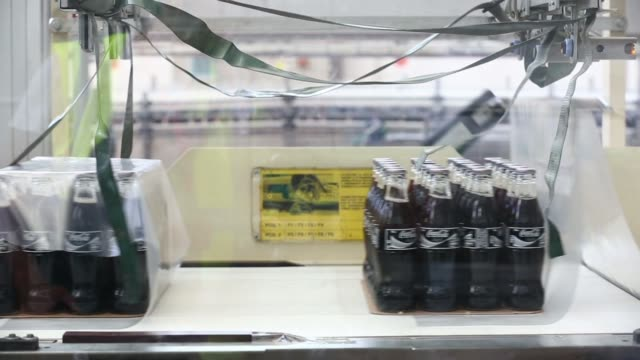 vídeos y material grabado en eventos de stock de a roll of coca cola labels sits in the forefround as glass bottles of coca cola light also known as diet coke move along the production line after... - diet coke