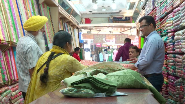 B Roll of fabrics and colourful Indian clothes at a shop
