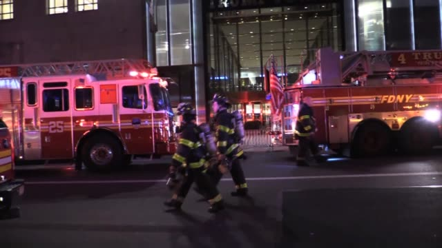 vidéos et rushes de roll of fire trucks in front of trump tower, night shots of fire trucks, shots of building pan down. - b roll